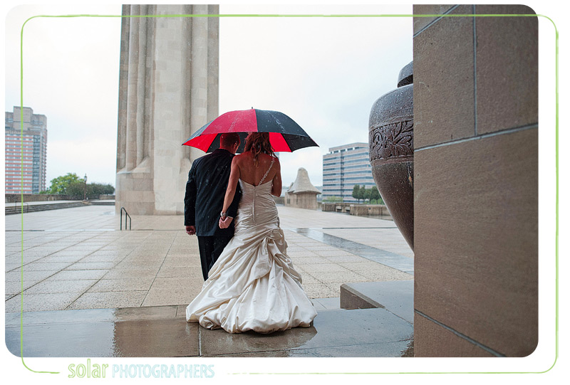 Bride and groom walk in the rain at Liberty Memorial in Kansas City on their wedding day.