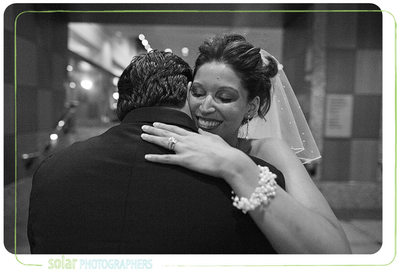 Bride hugs her husband.
