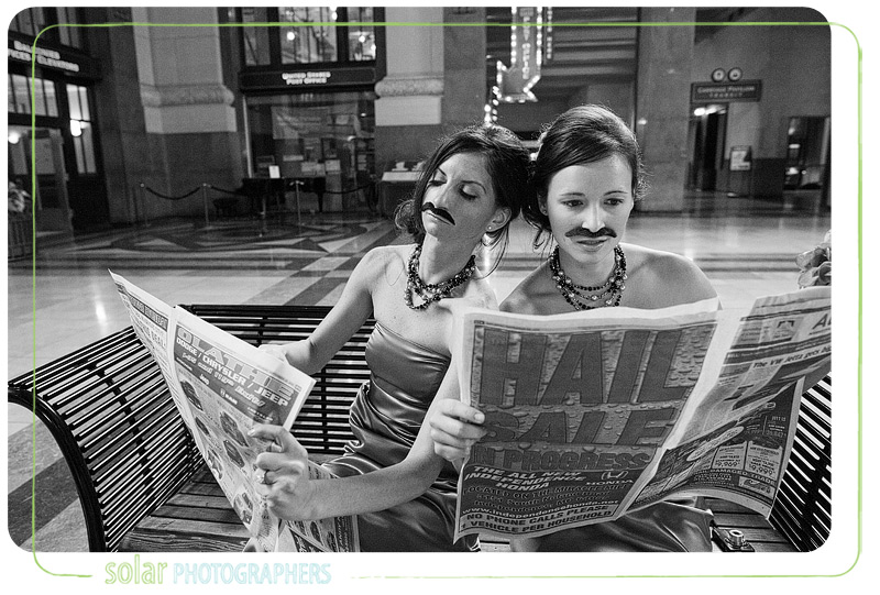 Bridesmaids in funny moustaches reading newspapers.