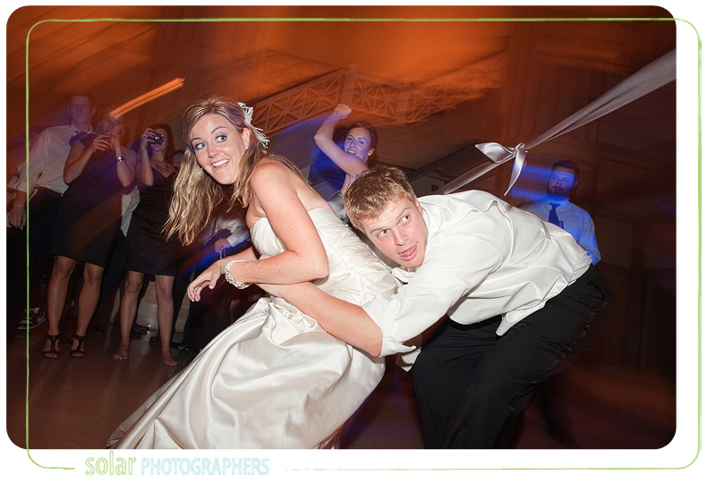 Bride and groom playing limbo at their wedding reception.