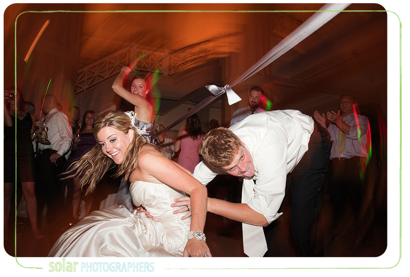 Bride and groom falling while playing limbo at their wedding reception.
