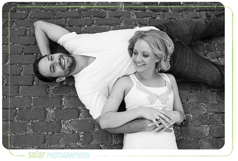 Couple laying on a brick road during their engagement session.