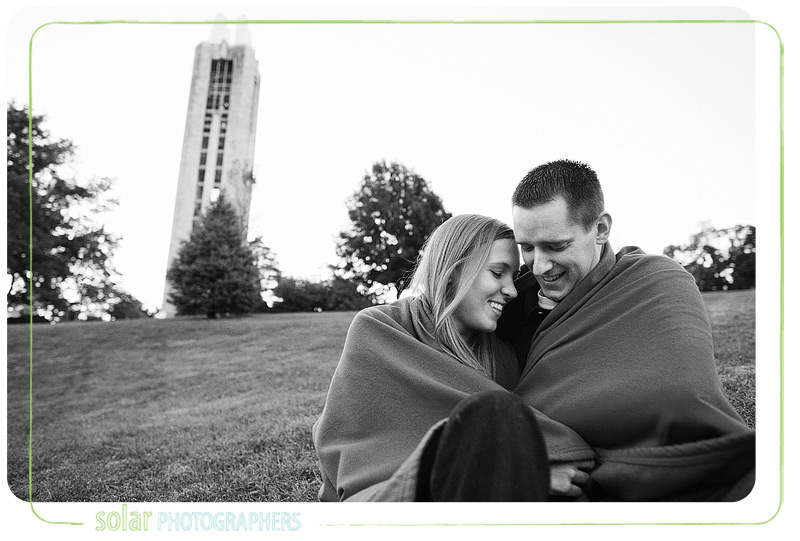 Couple snuggling by Campanile on KU campus in Lawrence.