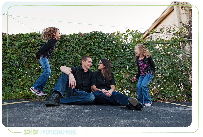 Fun family portrait with daughters jumping.