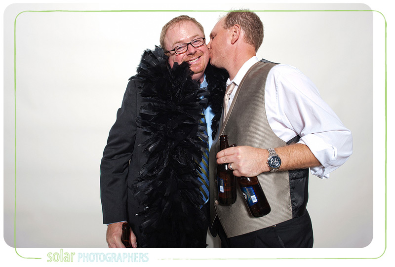 Two dudes kissing in the photo booth.