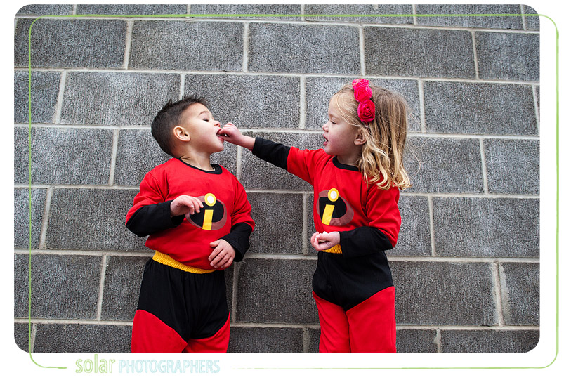 Kids dressed in Incredibles costumes feeding each other.