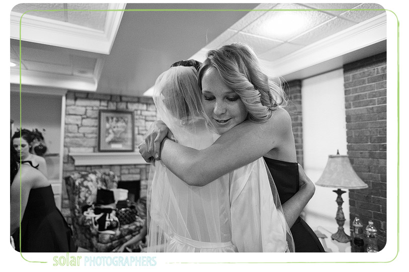 Sister hugs the bride.
