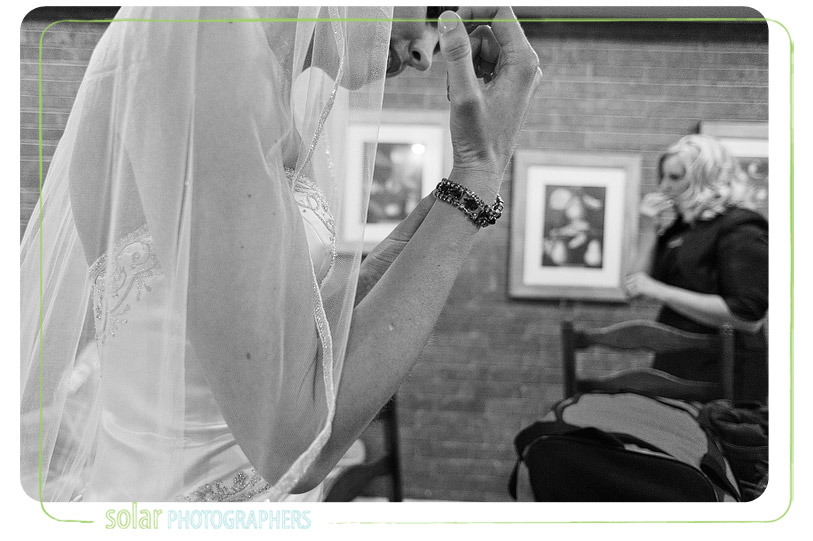 Bride putting on bracelet before her wedding.