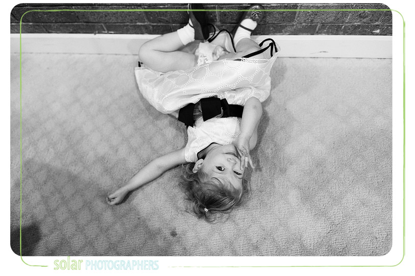 Cute flower girl laying on the floor.