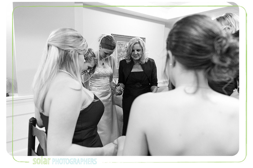 Bride prays with family and friends before her wedding.