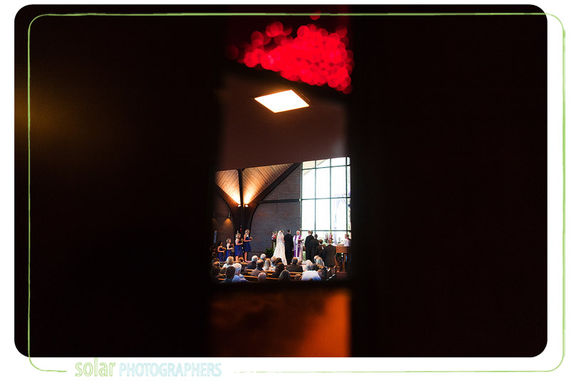 Wedding ceremony through the stained glass at Bethany Lutheran Church in Kansas City.
