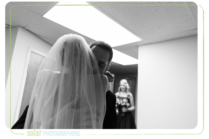 Man hugs his wife after their wedding ceremony.