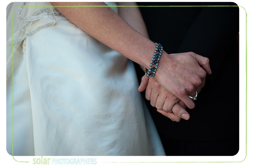 Bride holds grooms hands.