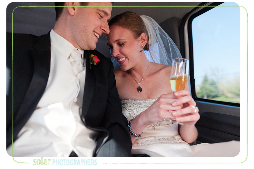 Bride and groom snuggling in the back of a limo.