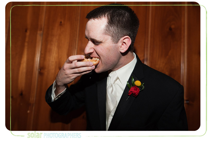 Groom eating donuts at an Ironwoods Lodge wedding reception.
