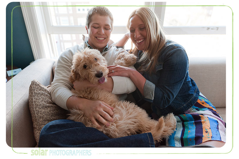 Couple laughing on the couch with their labradoodle puppy.