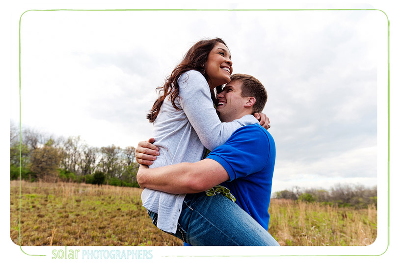 Couple laughing as she jumps into his arms.
