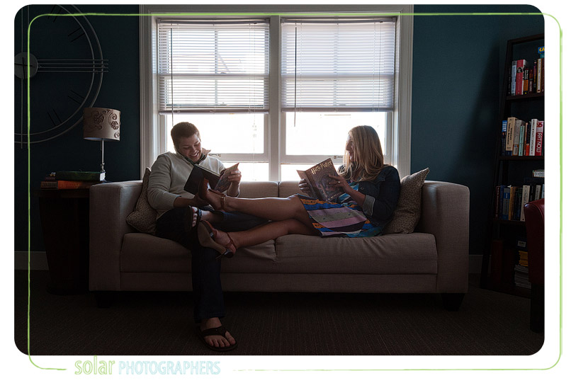 Couple on the couch reading Harry Potter books.