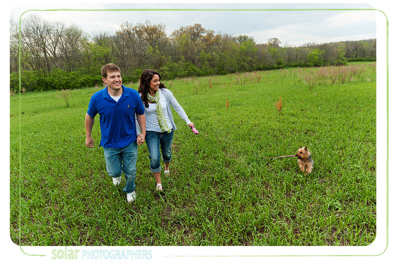 Couple running in a field with their dog.