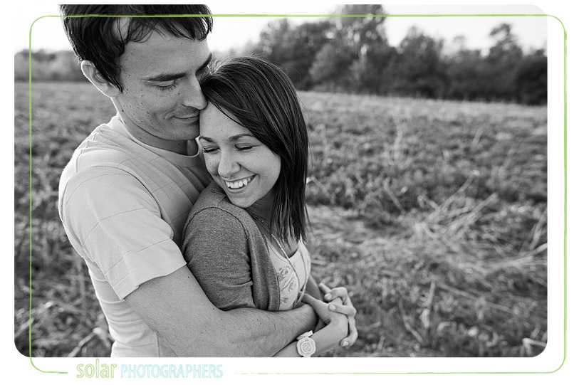 Man holding his fiancee smiling.