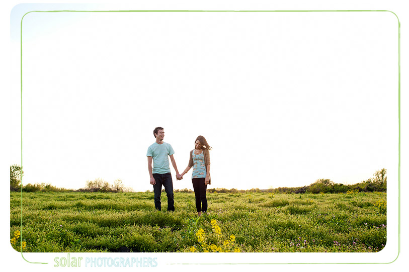 Couple holding hands in a field.