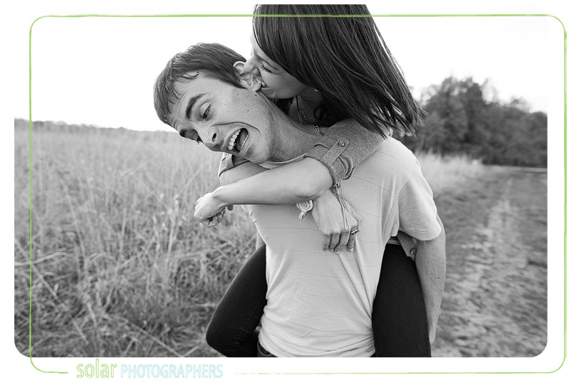 Woman biting man's ear and laughing.