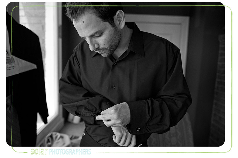 Groom fixing cufflinks at loose mansion in kansas city