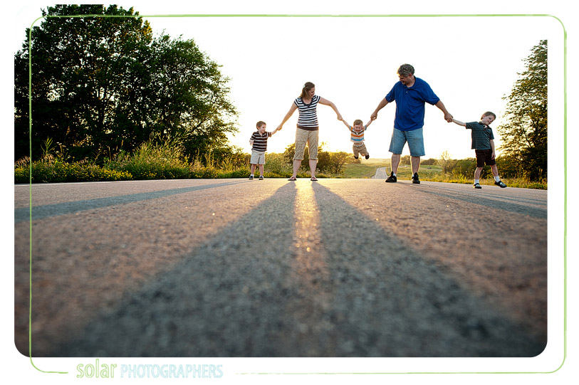 Family holding hands on a wide open road.