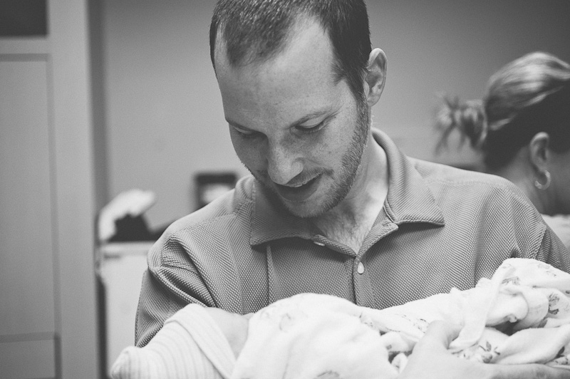 Dad holds his newborn baby girl.