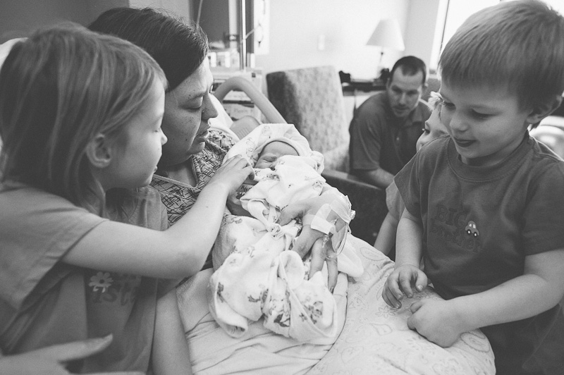 Siblings gather around their mom and their new baby sister.