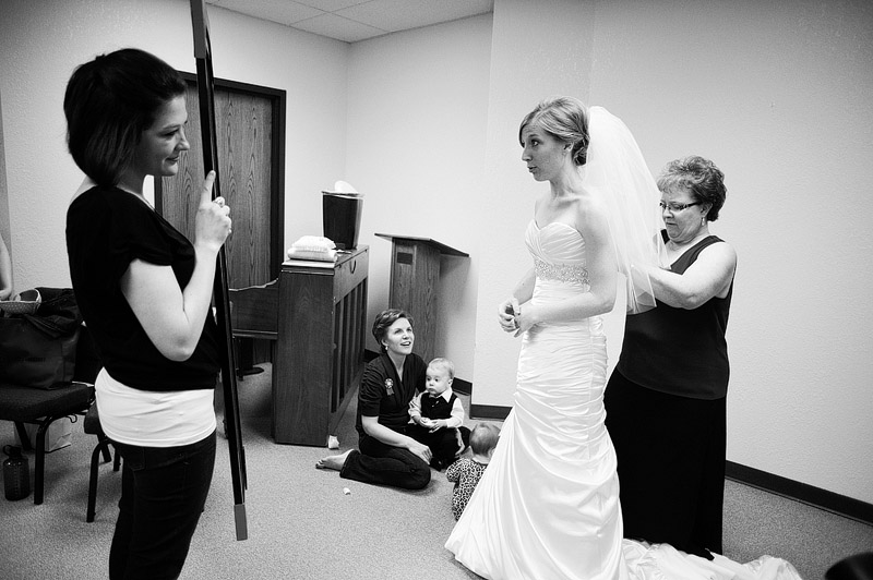 Mom helping daughter get into her wedding dress.