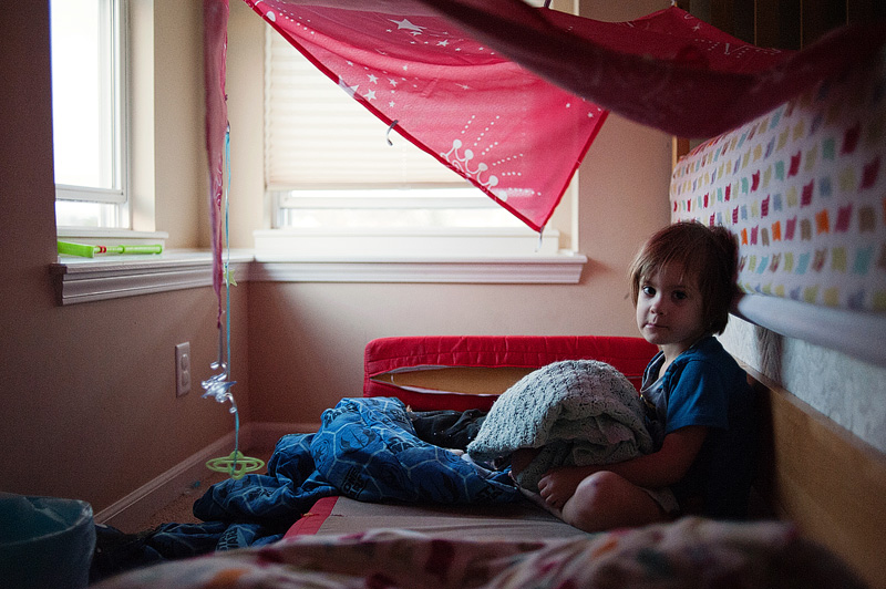 Girl sitting in a homemade fort with her favorite blanket.