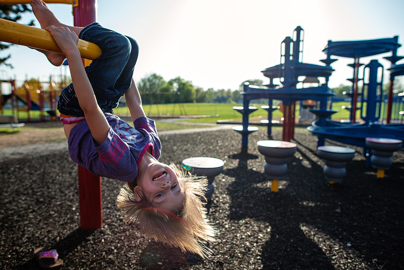 Girl hanging upside down on a playground.