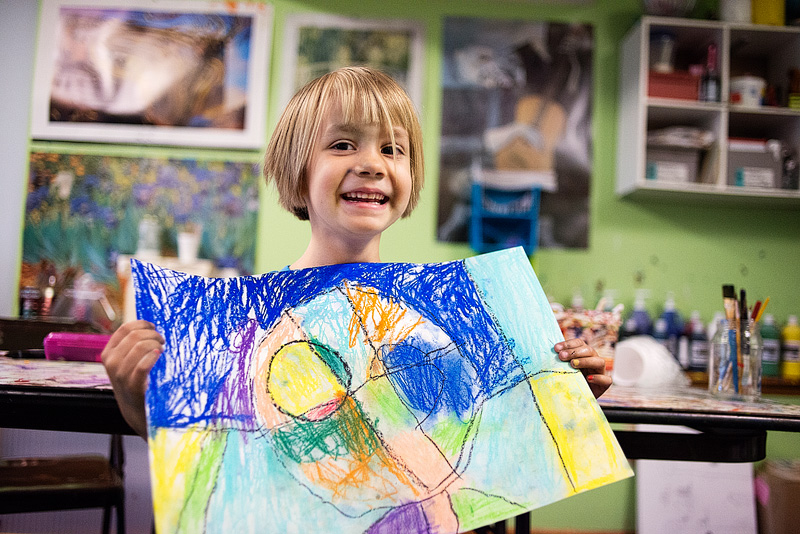 Ava holding up one of her art projects from art class.