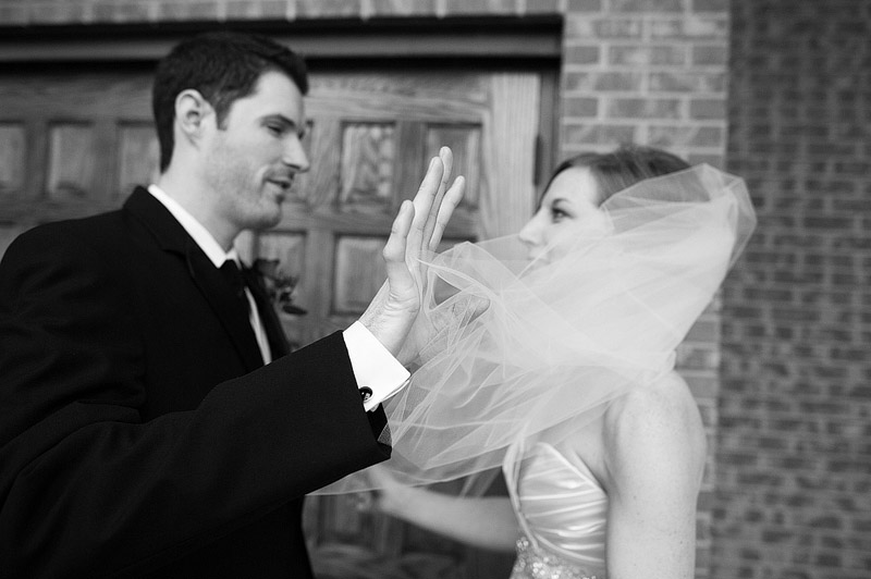 Groom brushes away bride's veil.