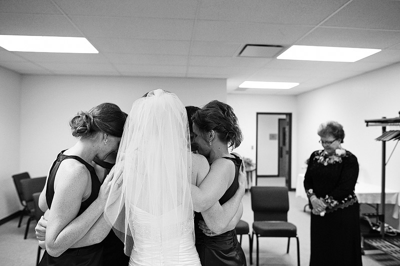 Bride praying with her bridesmaids before she gets married.