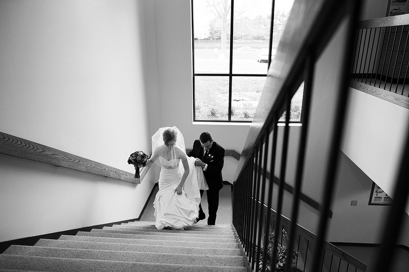 Father of the bride helping his daughter walk up the stairs in her wedding dress.