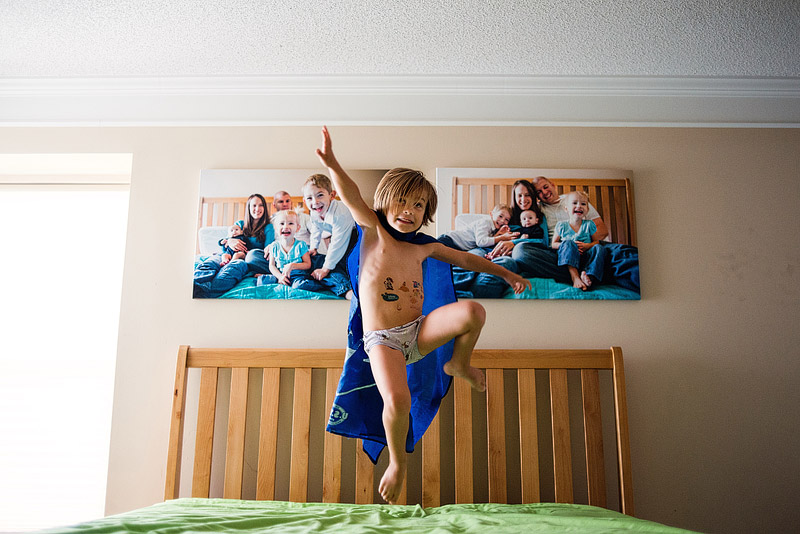 3 year old jumping on the bed.