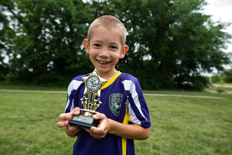 Boy holding his soccer trophy.