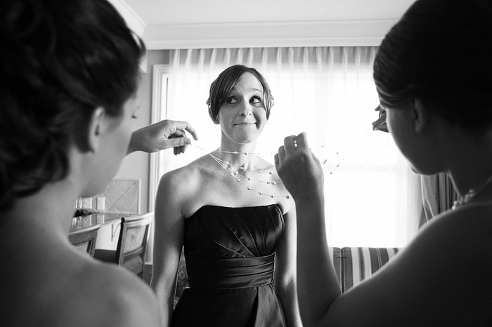 Bridesmaid getting jewelry on before the wedding.