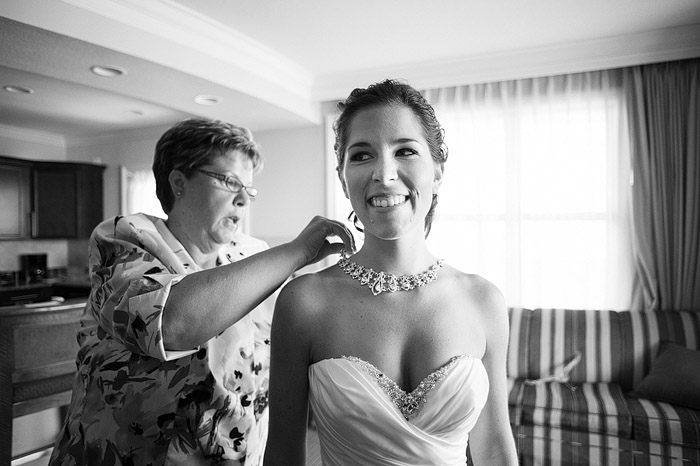 Mom putting jewelry on her daughter's wedding day.