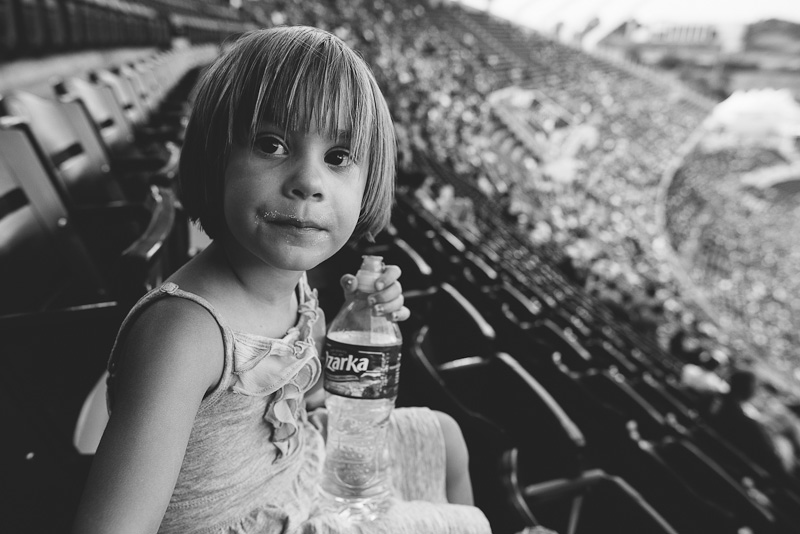 Girl sitting in the bleachers at Kauffman Stadium.