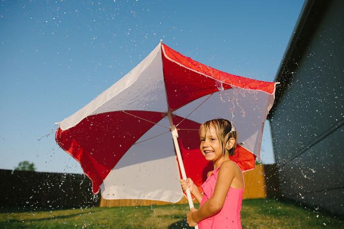 Girl holding an umbrella to block the hose.