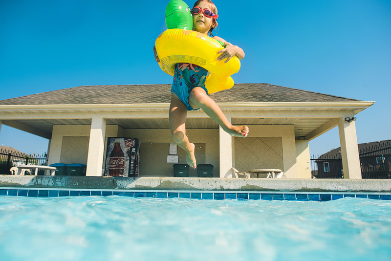 Girl jumping in the pool.