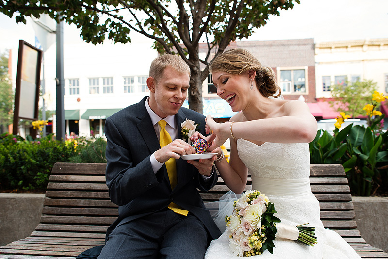 Bride and groom sharing a cupcake on their wedding day in Lawrence.