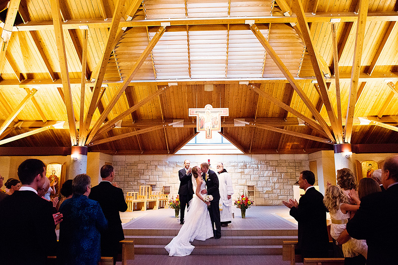 First kiss at a St. Lawrence Catholic Campus Center wedding in Kansas.