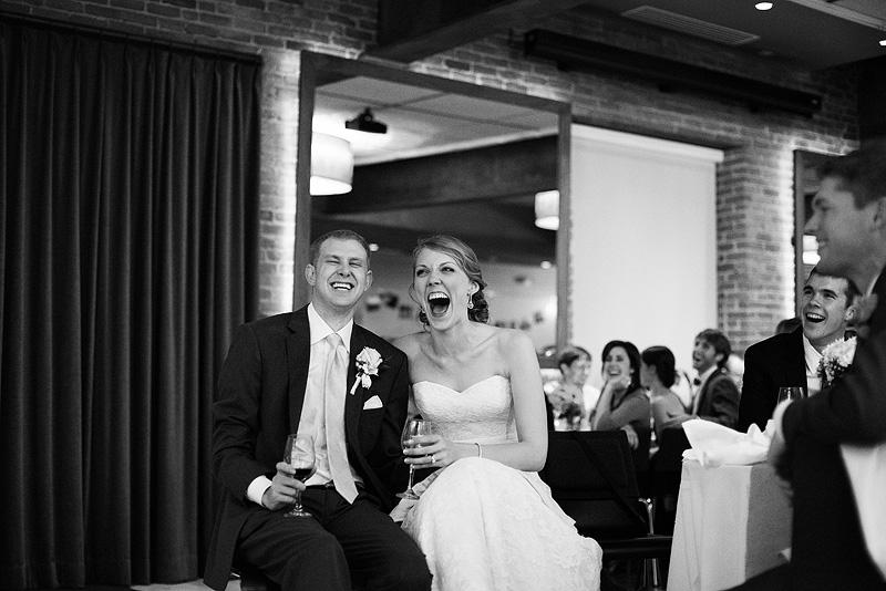 Bride and groom laughing during toasts at their Lawrence wedding reception.