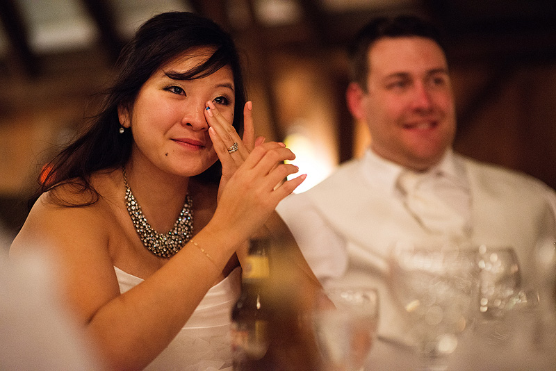 Bride crying during toasts at her wedding reception.