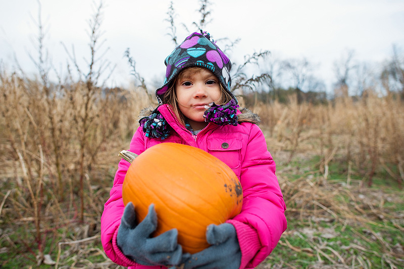 Girl holding her pumpkin from Powell's Pumpkin Patch.