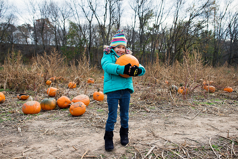 Girl holding her pumpkin from Powell's Pupmpkin Patch in Kansas.
